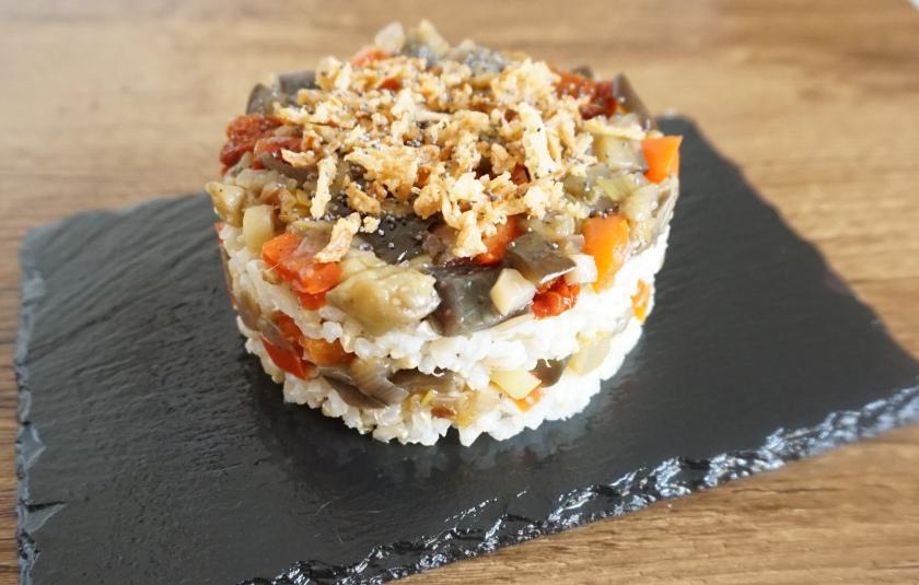Timbal de arroz integral y verduras con topping de cebolla crujiente y semillas de amapola
